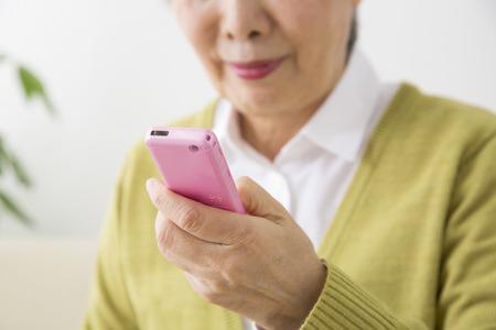 operates: Senior women who operates the mobile phone