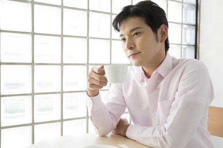 男性がコーヒーを飲む