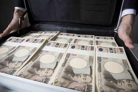 attache case: Men show a container with a lot of money in attache case