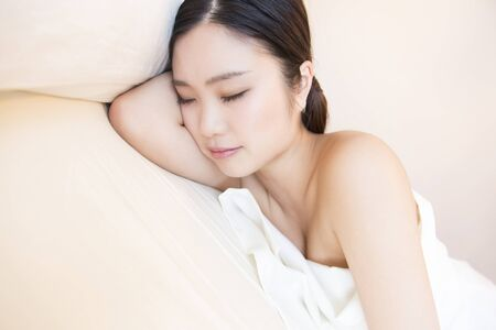 futon: Woman sleeping in a bed Stock Photo