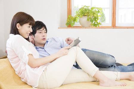 seres vivos: Pareja para ver la Tablet PC en el dormitorio Foto de archivo