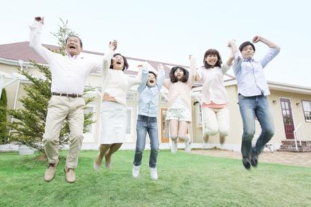 3 世代家族が庭にジャンプ