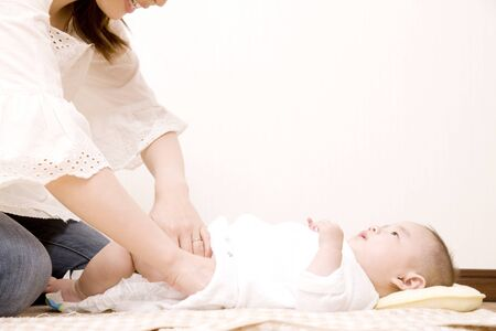 changing diaper: Mother changing the babys diaper Stock Photo