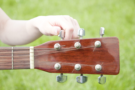 musical instrument parts: Hand woman to the tuning of the guitar in the grassland