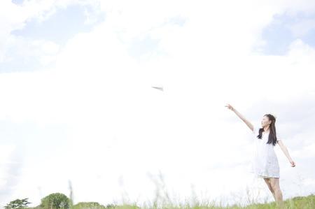 threw: Woman threw a paper airplane Stock Photo