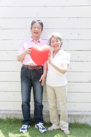 the place is outdoor: Senior couple with heart balloons Stock Photo