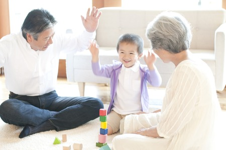old couple: Grandparents play with the grandson and building blocks