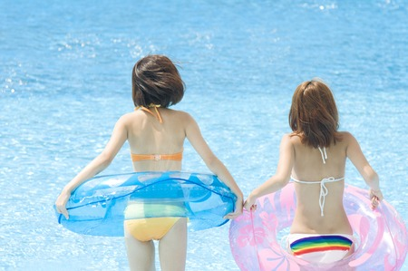 inner tube: Swimsuit 2 women of Rear playing in the pool with a inner tube Stock Photo