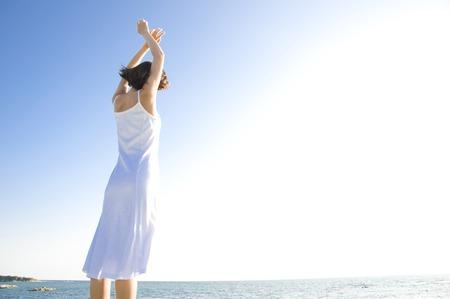 女性の背面を海辺でストレッチ