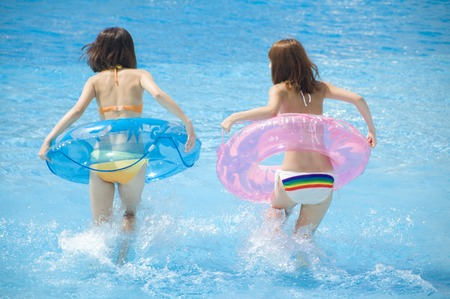 Swimsuit 2 women of Rear playing in the pool with a inner tube Imagens