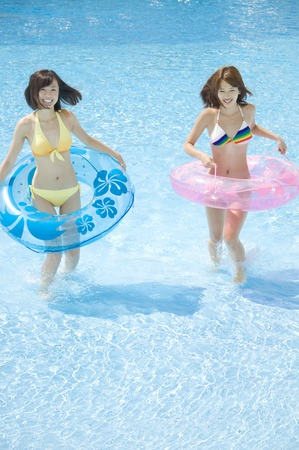 inner tube: Two swimsuit woman playing in the pool with a inner tube