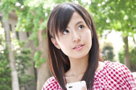 inwardly: Women smile inwardly cheek with a smartphone