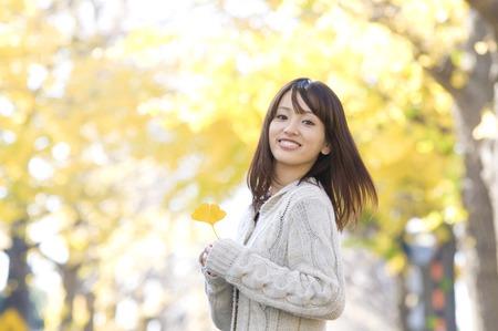 ginkgo leaf: Women smile looking back has a ginkgo leaf