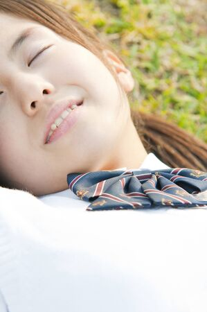 lie down: Schoolgirl to lie down on the grass Stock Photo