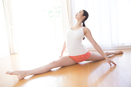 pliable: Woman stretching in your living room Stock Photo
