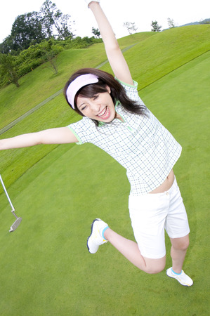 putter: Woman to jump with a putter Stock Photo