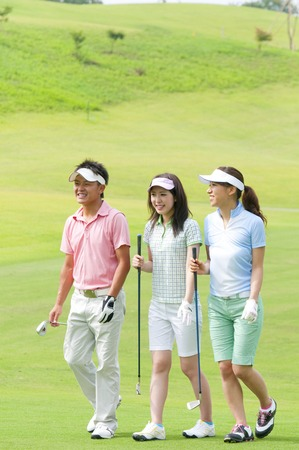 Men and women walk the golf courses Stock Photo