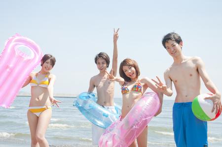 frolic: Men and women frolic on the beach
