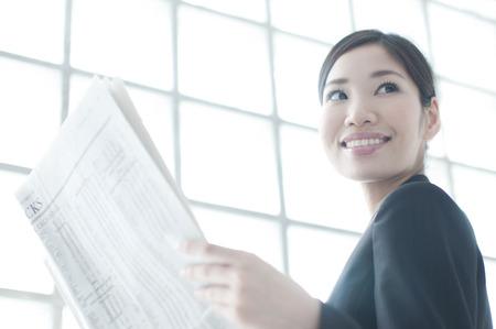 OL 笑顔や新聞を読む 写真素材