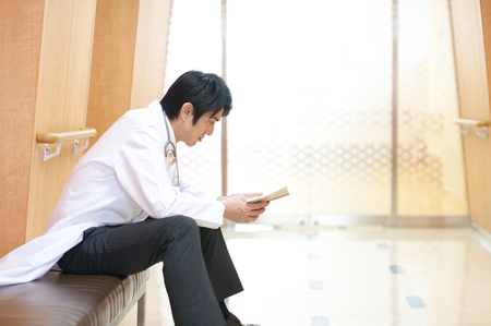 latency: Male doctor reading a book Stock Photo