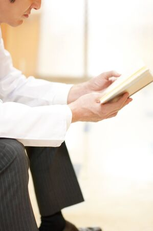 latency: Hand of male doctor reading a book