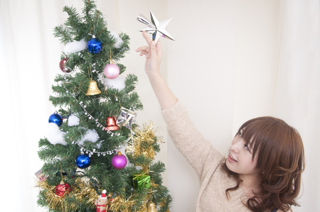 decorate: Women decorate the Christmas tree