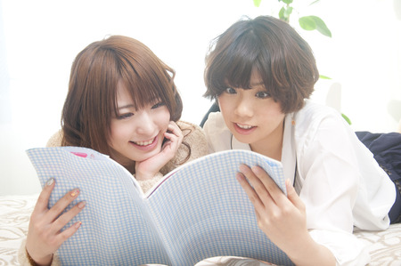 2 women reading a book Stock Photo