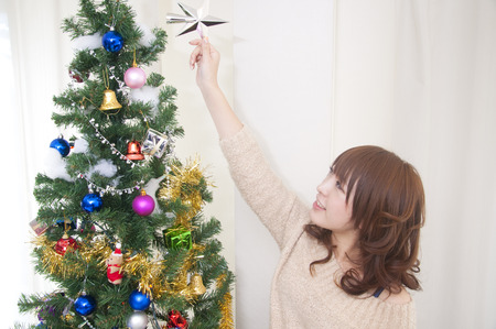 Women decorate the Christmas tree photo
