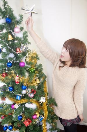 Women decorate the Christmas tree photo