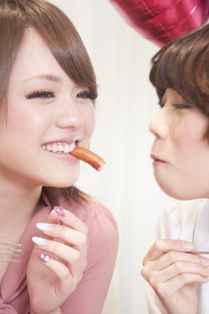 proceeding: 2 women proceeding eat sausage each other