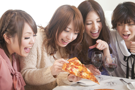 4 women surrounding the pizza