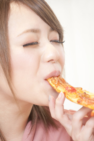 oneself: Women stuff oneself a pizza Stock Photo