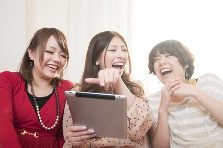 reir: Tres mujeres que ríen mientras ve un Tablet PC