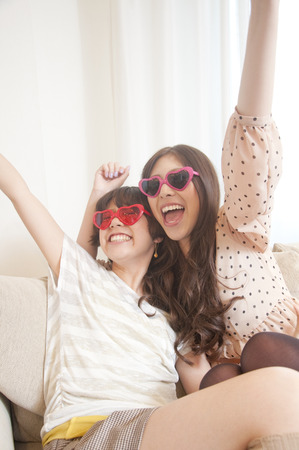 rollick: Two women frolic it with sunglasses
