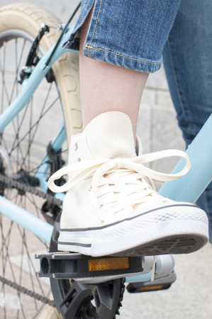 bicycle pedal: Feet of a woman stepping on the bicycle pedal Stock Photo