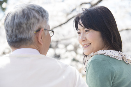 Senior couple to each other staring under the cherry tree