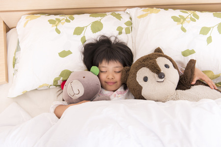 Girl sleeping while holding a stuffed toy