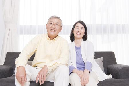 先輩カップルの笑顔がソファーに座って