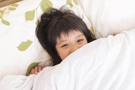 futon: Girl to hide the face in the futon Stock Photo