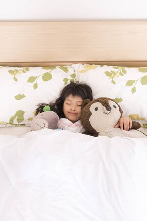 article of clothing: Girl sleeping while holding a stuffed toy Stock Photo