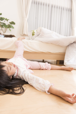 tumble down: Girl sleeping while tumbled down from the bed Stock Photo