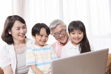 exert: Grandparents and grandchildren to touch the notebook PC Stock Photo