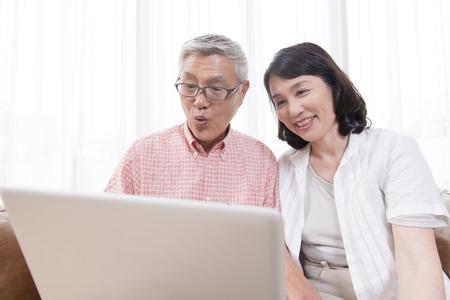 exert: Senior couple touching the notebook PC