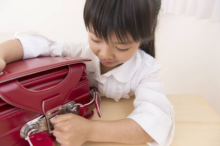 writing instrument: Girl to put the writing instrument in school bag