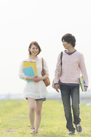 Men and women smile walking with textbooks
