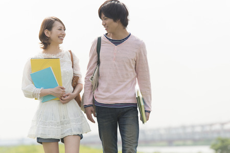 Men and women smile walking with textbooks photo