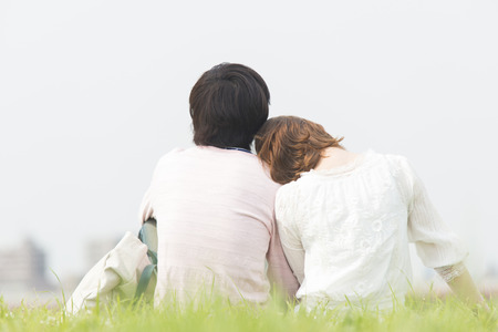 snuggle: Men and women sit down snuggle up lawn Stock Photo