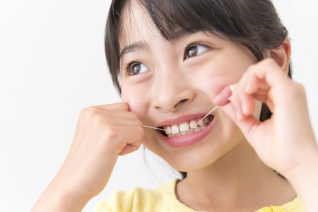 Girl to use dental floss Stock Photo