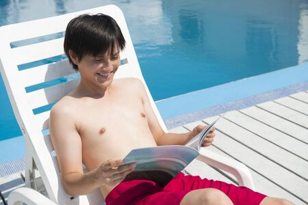 read magazine: Male swimsuit Read magazine sitting on summer bed