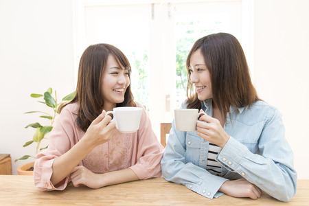 shopping buddies: 2 women to each other staring while drinking coffee